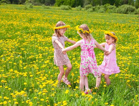 niños danzando: Tres niñas llevaba corona de diente de León disfruta de un día de verano al aire libre