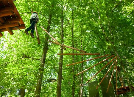 School jongen klimmen in avontuurlijk park