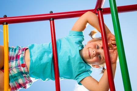Klettergerüst Monkey Bar : Lächelnde junge hängen vom klettergerüst auf spielplatz stockfoto