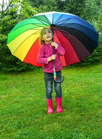botas de lluvia: Niña con botas de goma roja que oculta detrás de coloridos paraguas en la lluvia