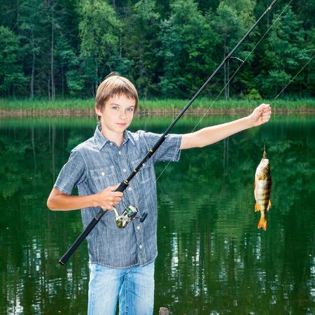 Cute boy showing fish he caught while fishing photo