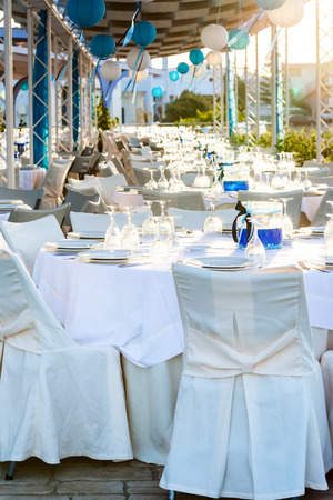 arranging: Table setting for an event party at outdoor cafe Stock Photo
