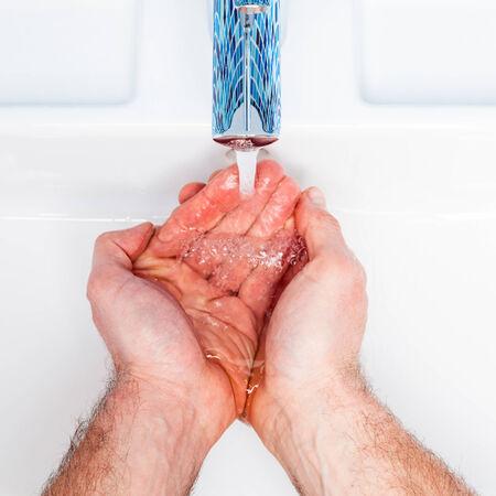 lavandose las manos: Hombre que se lava las manos en un lavabo del baño