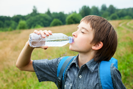 water activity: Boy drinking water from pet bottle outdoors
