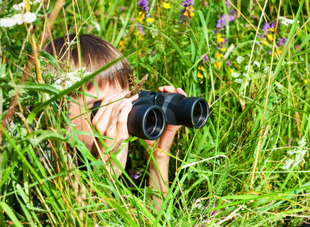 schoolkid search: Boy hiding in grass looking through binoculars outdoor Stock Photo