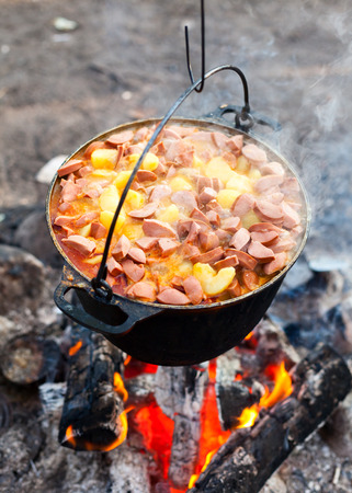Cooking potatoes with sausages on a campfire