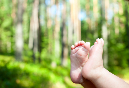 feet soles: Little child gets his feet into the fresh air in a summer forest
