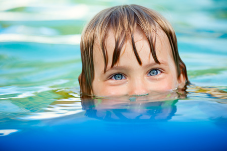 Little girl swimming in a pool photo