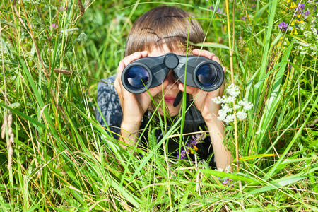 Boy hiding in grass looking through binoculars outdoor Фото со стока