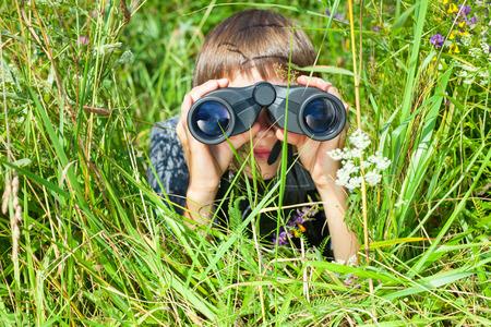 Boy hiding in grass looking through binoculars outdoor Standard-Bild