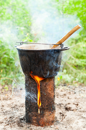 finnish: Cooking Goulash soup in cauldron on Finnish (Swedish) log stove