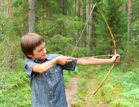 Boy aiming home-made wooden bow outdoors 스톡 콘텐츠
