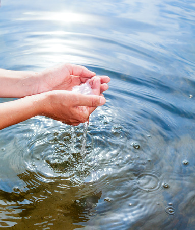 hands cupped: Woman taking clear water at a lake by hands Stock Photo