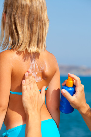 Mother applys sunblock cream on daughters back photo