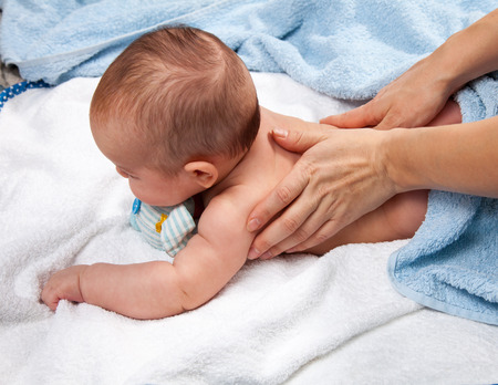 Masseuse massaging 5 months infant photo