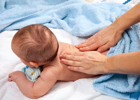 masseuse: Masseuse massaging 5 months infant