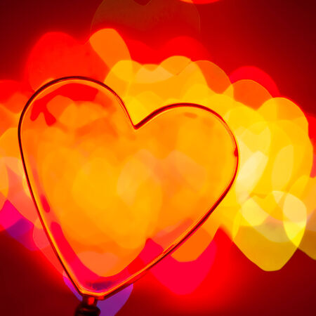 plastic heart: Red transparent plastic heart with blured lights in background, very shallow DOF Stock Photo