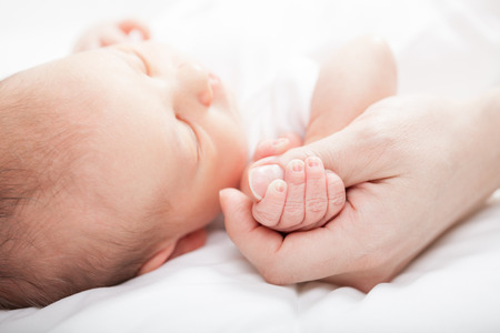 Newborn baby holding mother's thumb Archivio Fotografico