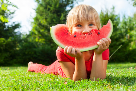 melon fruit: Happy little girl with watermelon in a garden