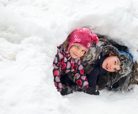 snowbank: Young boy and girl hiding in a snow cave they made