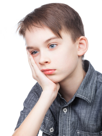 one boy only: Portrait of upset kid holding his head on white background