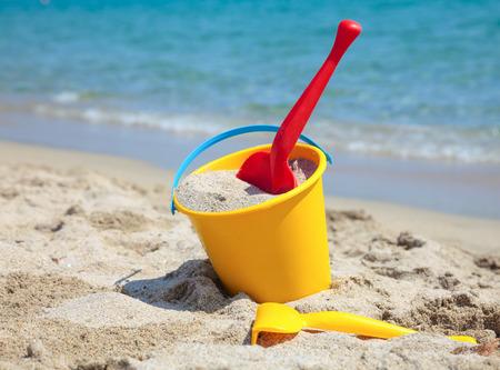 해변에 노란색 모래 양동이와 삽