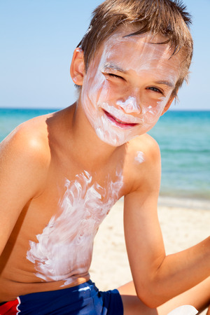 Child applied too much of sunblock cream Standard-Bild