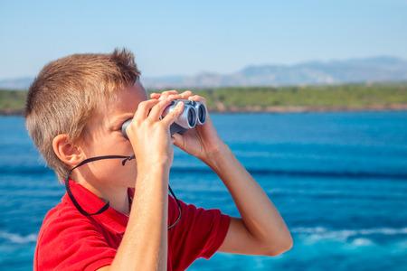 schoolkid search: Vela Boy en crucero mirando a trav�s de binoculares