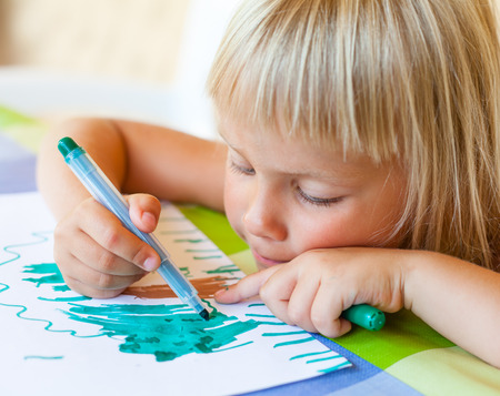 Cute little girl sitting at a table drawing photo
