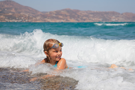 swim goggles: Happy little girl wearing swim goggles lying in the sea