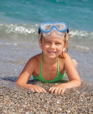 Happy little girl wearing snorkeling mask lying in the sea photo