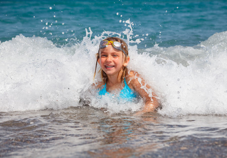 swim goggles: Happy little girl wearing swim goggles playing in the sea