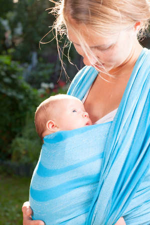 Mother carrying her child in a baby sling photo