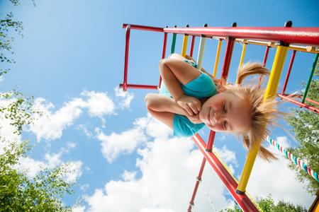 climbing frame: Inquadratura dal basso di ragazza bionda carina che indossa tshirt blu appeso a un bar scimmia. La ragazza sta sorridendo con gli occhi chiusi. Il telaio di arrampicata � dipinto in rosso giallo verde e situato nel cortile di una casa. Blu cielo estivo con nuvole e albero Archivio Fotografico
