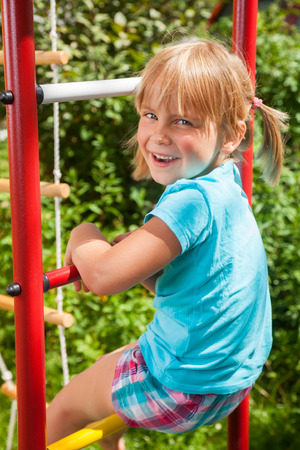 children play area: Portrait of cute blond girl with blue eyes wearing blue tshirt sitting on monkey bars on a summer day. Girl looking at camera smiling. The climbing frame is located in the courtyard of a house. Green leaves a seen in the background.