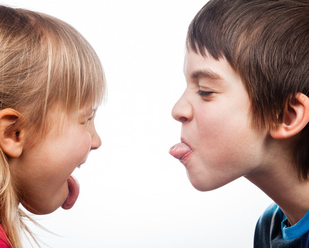 Close-up shot of boy and girl sticking out tongues to each other on white background. Children are half-siblings.