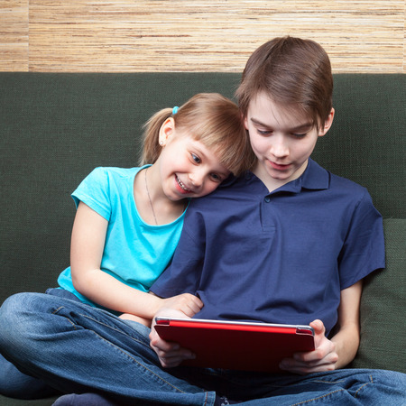 Children wearing casual clothes playing or watching a movie on a touch pad at home sitting on a green sofa. Boy and girl are half-siblings. Brother is holding tablet with red cover. They are looking at screen smiling. photo