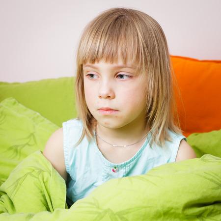 varicela: Retrato de malestar 6 años chica rubia sentada en su cama con una erupción de la varicela en su cara