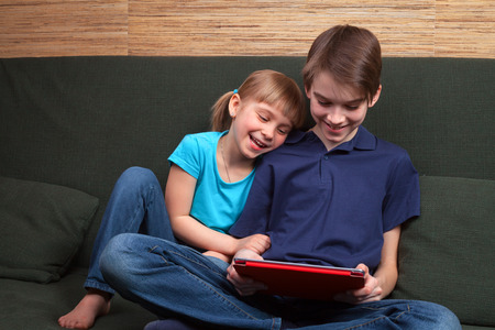 brother sister: Children wearing casual clothes playing or watching a movie on a touch pad at home sitting on a green sofa. Boy and girl are half-siblings. Brother is holding tablet with red cover. They are looking at screen smiling.