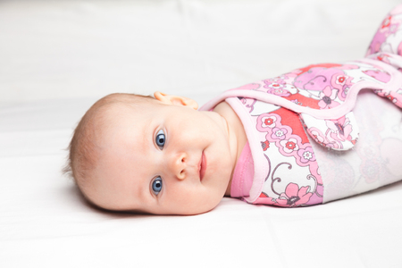 swaddling: Three month baby girl wrapped in a modern winged baby swaddle laying on a bed. Swaddling is a practice of wrapping infants in cloths in order to prevent limb movement. Medical and psychological effects of swaddling are controversial. Stock Photo