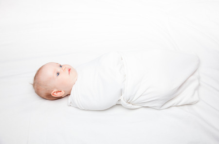 Three month baby girl swaddled in white blanket laying on a bed. Swaddling is a practice of wrapping infants in cloths in order to prevent limb movement. Medical and psychological effects of swaddling are controversial.