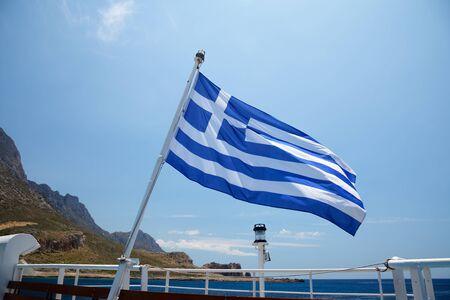 greece: Flag of Greece on a cruise ship against greek coastline Stock Photo