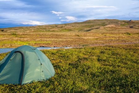 camping pitch: Camping tent on a river shore in Iceland Stock Photo