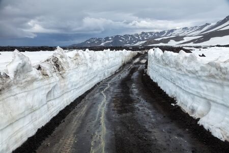 unsurfaced road: Dirt road in Iceland with snow walls Stock Photo