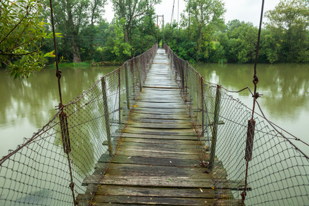 rickety: Rickety foot bridge over muddy water Stock Photo