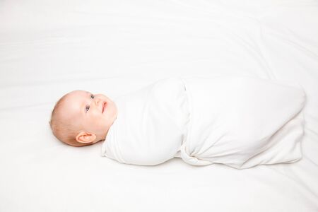 swaddle: Three month baby girl swaddled in white blanket laying on a bed. Swaddling is a practice of wrapping infants in cloths in order to prevent limb movement