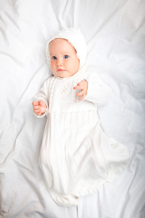 baptize: Close-up shot of six month baby girl wearing white christening clothes laying on a bed Stock Photo