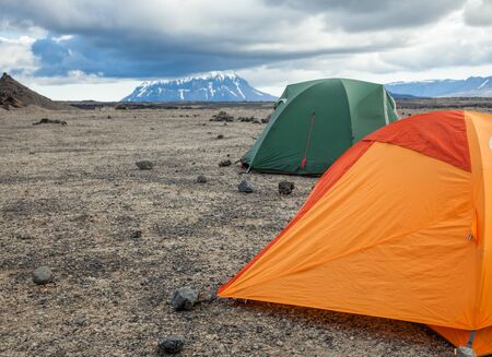 camping pitch: Camping tents on a rocky campsite in Iceland with Herdubreid in background