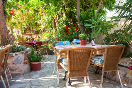 europeans: Tables with chairs at shaded cafe terrace in Crete