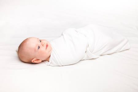 Three month baby girl swaddled in white blanket laying on a bed. Swaddling is a practice of wrapping infants in cloths in order to prevent limb movement